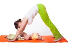 Yoga för moder för ung kvinna behandla som ett barn praktiserande med Arkivbild