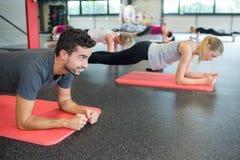 Yoga för planka för sida för gruppfolk poserar praktiserande Arkivfoto