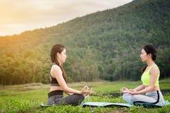 Yoga för två kvinnor i parkera, vård- kvinna, yogakvinna Begrepp av royaltyfri bild