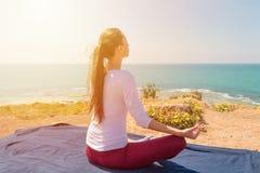Yoga för ung kvinna på havsstranden Fotografering för Bildbyråer