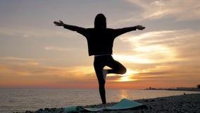 Yoga f?r ung kvinna f?r kontur ?vande p? solnedg?ngen p? havet Lyckliga ?gonblick av liv - konturyoga p? stranden p? stock video