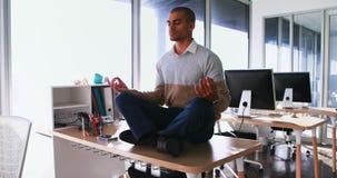 Yoga facente esecutiva maschio in ufficio 4k stock footage