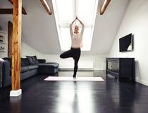Yoga facente femminile a casa Fotografie Stock Libere da Diritti
