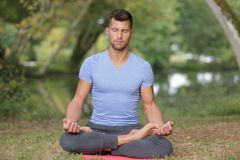 Yoga facente maschio di forma fisica in parco immagine stock