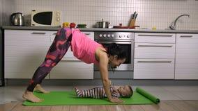 Yoga faisant femelle convenable ainsi que le bébé à la maison banque de vidéos