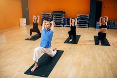 Yoga, female group with instructor in motion stock images