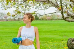 Yoga and fitness. Beautiful woman is holding a yoga mat outdoors royalty free stock images