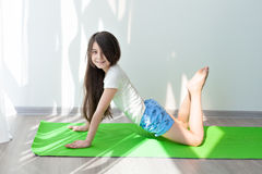 Yoga and fitness for kids.. Little girl doing gymnastics on a green yoga mat. children's fitness and yoga for children. fitness exercises and stretching Stock Photo