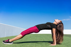 Yoga fitness woman planking in upward plank pose. Yoga fitness woman stretching body in upward plank pose doing reverse planking exercise on outdoor grass park Stock Photo