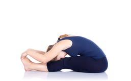 Yoga forward bending pose. Yoga paschimottanasana full forward bending pose by beautiful Caucasian woman in blue Capri and top at white background. Free space Stock Photography