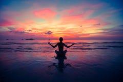 Yoga för ung kvinna för kontur praktiserande på stranden på solnedgången relax Fotografering för Bildbyråer