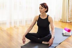Yoga-Frau auf Sport Mat Indoors stockbild