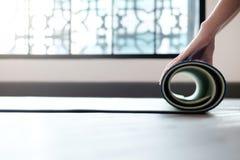Yoga-Frau, die ihre lila Matte nach einer Yogaklasse rollt Lizenzfreie Stockfotografie