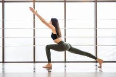 Yoga-Frauenpraxis Virabhadrasana schöne nahe Fensteryogaraum-Studiohintergrund Lokalisiert auf Weiß stockbilder