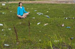 Yoga in garbage. Woman practises yoga on the littered lawn stock photos