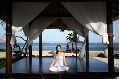 Yoga in a Gazebo. Woman meditating inside a gazebo stock photo