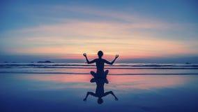 Yoga, geschiktheid, gezonde levensstijl Het meisje van de silhouetmeditatie op de achtergrond van het overweldigende overzees en  Stock Afbeelding