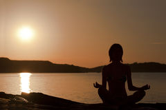 Yoga girl. Seated yoga pose. Sunset silhouette Stock Photography