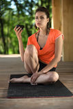 Yoga girl with cup. Handsome girl sits on the black yoga mat on the wooden terrace on the nature background. Her head is partially turned to the right, right Royalty Free Stock Image
