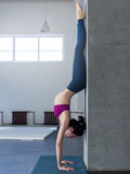 Yoga girl doing handstand with backbend exercise in gym Stock Photography