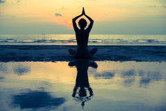 Yoga. Girl doing meditation near the ocean beach. Stock Image