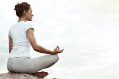 Yoga girl making a dzen or zen and smilling. Stock Photos