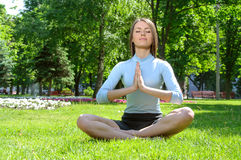 Yoga girl meditates in the lotus position Stock Photos