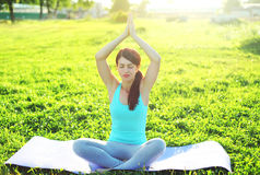 Yoga girl meditates sitting on grass pose lotus in summer Royalty Free Stock Photo