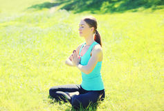 Yoga girl meditates sitting on grass in sunny summer day Stock Images
