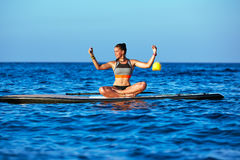 Yoga girl over SUP Stand up Surf board Royalty Free Stock Photography