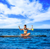 Yoga girl over SUP Stand up Surf board Royalty Free Stock Image