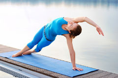 Yoga girl practicing side plank positing at the river bank in th Stock Image