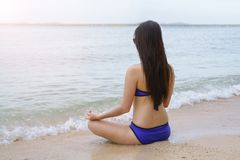 Yoga girl sitting in lotus pose on the beach Royalty Free Stock Photo