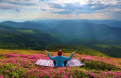 Yoga girl is sitting on the striped rug in meditation. Yoga girl is sitting on the striped rug in meditation on the lawn with pink flowers at the high mountains Royalty Free Stock Photo