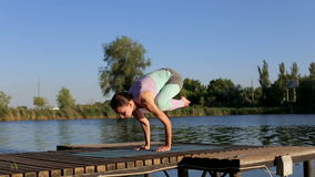 Yoga. Girl is standing on her hands doing yoga. stock video footage