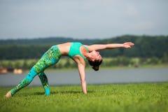 Yoga girl training outdoors on nature background. Stock Image