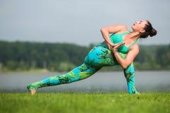 Yoga girl training outdoors on nature background. Royalty Free Stock Images