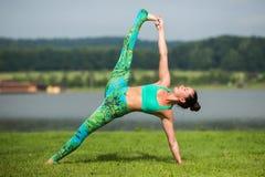 Yoga girl training outdoors on nature background. Stock Photo
