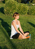 Yoga on the Grass. A beautiful slim young woman either taking a break from exercise or yoga, sitting in a field, surrounded by green Stock Photography