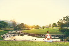 Yoga on grass. Yoga at park with view of the mountains, with sunlight. Young woman in lotus pose sitting on green grass. Concept of calm and meditation Royalty Free Stock Photos