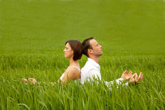 Yoga green couple. Couple relaxing in yoga position in green meadow field Stock Photography