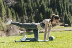 Yoga on a green lawn. The girl on a green lawn practices yoga, costs in a pose Stock Images