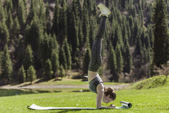 Yoga on a green lawn. The girl on a green lawn practices yoga, pose on the head Stock Photography