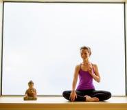 Yoga-Haltung herein auf Fensterbrett Lizenzfreie Stockbilder