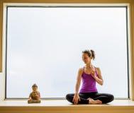 Yoga-Haltung herein auf Fensterbrett Stockfotos