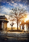 Yoga in Hampi. Man doing yoga near ancient ruins on Hemakuta hill in Hampi, Karnataka, India stock photo
