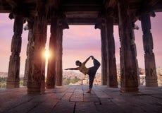 Yoga in Hampi temple. Woman doing yoga in ruined ancient temple with columns, Hampi, Karnataka, India stock photo
