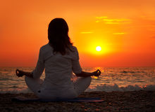Yoga hand. Woman Practicing Yoga near the Ocean at Sunset Royalty Free Stock Photo
