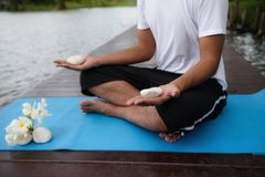 Yoga hand meditation exercise near pond. Yoga hand meditation exercise with white rock at wood bridge near pond during summer. Healthcare and Fitness concept Stock Photos