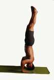 Yoga Handstand Isolated. Male back in gray shorts finding zen through yoga in a handstand on a green matt Stock Photos